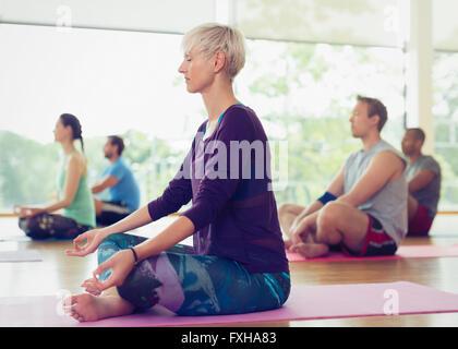 Gelassene Frau im Lotussitz in Yoga-Kurs - Stockfoto