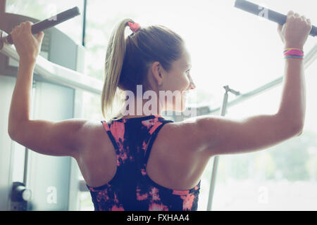 Fit Woman Lat Pulldowns an Geräten im Fitnessstudio zu tun - Stockfoto