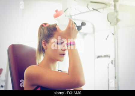 Müde Frau Kühlung Stirn mit Wasserflasche in Turnhalle - Stockfoto