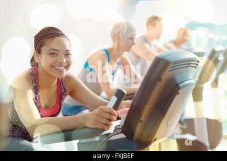 Porträt, lächelnde Frau Reiten Heimtrainer in Turnhalle - Stockfoto