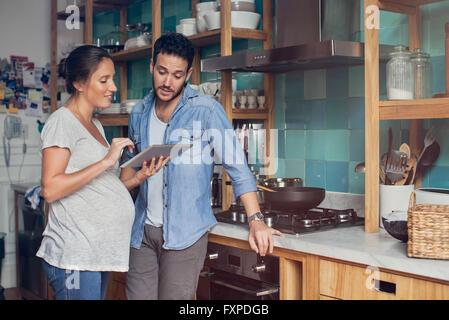 Paar in Küche, Blick auf digital-Tablette zusammen - Stockfoto