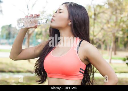 Asiatische Fitness Frau Trinkwasser im park - Stockfoto