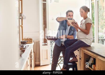 Paar verweisen auf digital-Tablette während der Zubereitung - Stockfoto