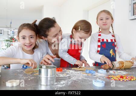 Mädchen mit Mutter am Küchentisch machen Cookies lächelnd - Stockfoto
