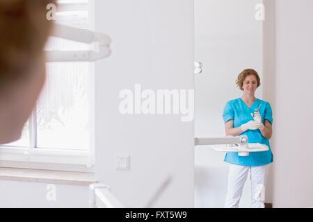 Zahnarzthelferin in Zahnklinik Vorbereitung Spritze lächelnd Schutzhandschuhe tragen - Stockfoto