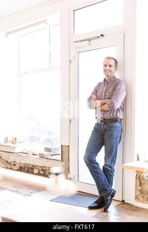 Voller Länge Blick auf reifer Mann gelehnt Tür Arme gefaltet, Blick auf die Kamera zu Lächeln - Stockfoto