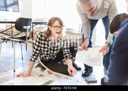 Architekten auf Büroetage diskutieren Blaupause lächelnd - Stockfoto