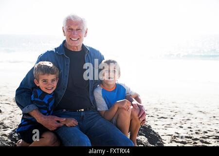 Großvater mit zwei Enkel, sitzen am Strand, Lächeln - Stockfoto