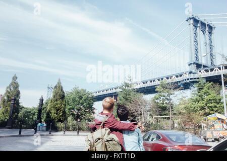 Rückansicht des männlichen Partner nehmen Selfie vor Manhattan Bridge, New York, USA - Stockfoto