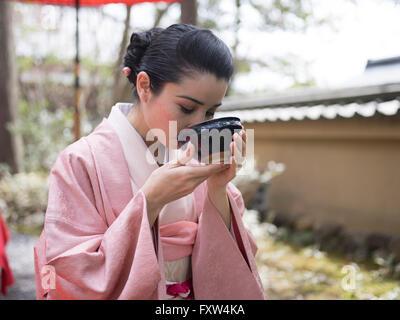 Japanische Frau im Kimono eine Schale mit grünem Tee zu trinken, in den Gärten des Kinkaku-Ji, ein Zen-buddhistischen - Stockfoto