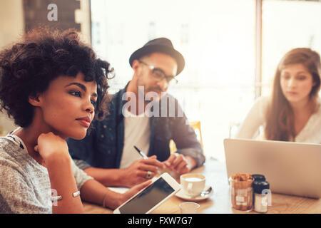 Porträt des jungen Afrikanerin mit digital-Tablette und Menschen im Hintergrund an einem Cafétisch hautnah. Junge - Stockfoto