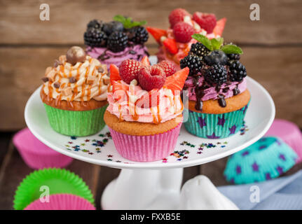 Reihe von verschiedenen leckeren Cupcakes auf lustige Kuchenplatte - Stockfoto