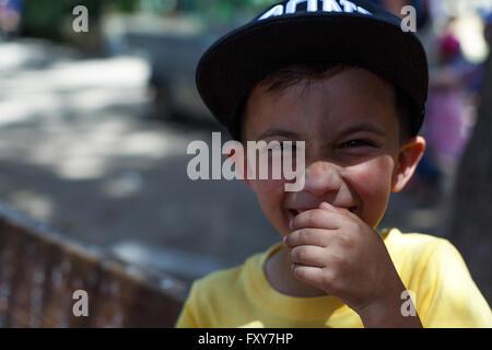 Brünette kaukasischer junge lächelnd mit Arme gekreuzt tragen flache Kappe - Stockfoto
