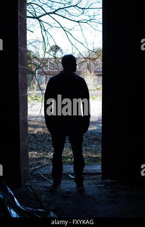 Silhouette eines Mannes in der Tür eines verlassenen Gebäudes stehe