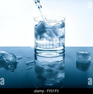 Wasser kühlen Drink über hellen Hintergrund in Glas gießen. Blaue farbige Bild - Stockfoto