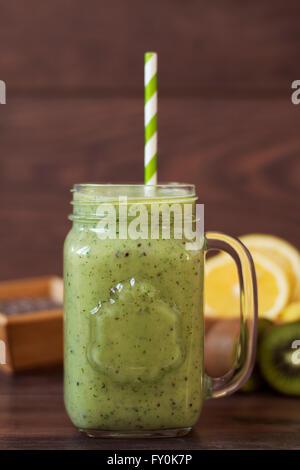 Gesunde Smoothie Kiwi. Milchshake mit Kiwi, Spinat, Banane, Zitrone, Chia-Samen. Holz-Hintergrund - Stockfoto