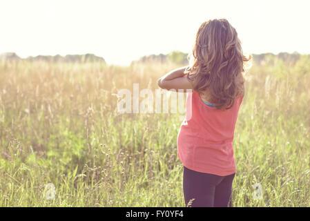 Junge schöne schwangere Frau halten Bauch lächelnd, in rot ein Leichtes Sommerkleid, glücklich auf der Wiese den - Stockfoto