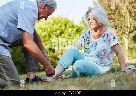 Alter Mann hilft Frau mit verstauchten Knöchel in der Natur - Stockfoto