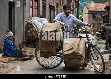 Ein Mann mit einem alten Fahrrad und eine Frau spinnt Wolle in dem kleinen Dorf Bungamati, Nepal - Stockfoto