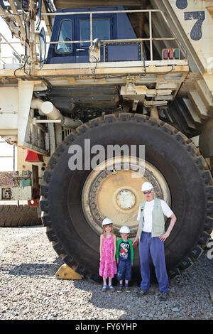 Ein Mann und zwei Kindern in den Schatten gestellt durch enorme mine LKW-Reifen. - Stockfoto