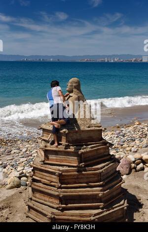 Mexikanische Künstlerin stehend auf Formen beim Schnitzen einer Sandskulptur am Strand am Malecon in Puerto Vallarta - Stockfoto