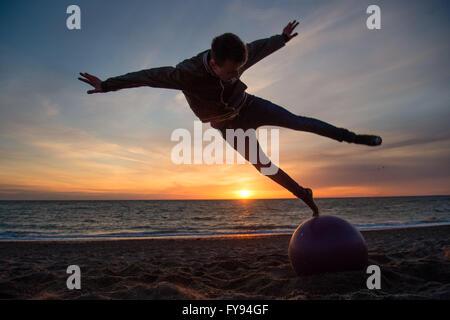Aberystwyth Wales UK, Samstag, 23. April 2016 UK Wetter: wie die Sonne über Cardigan Bay in Aberystwyth am Ende eines Tages voller Sonnenschein aber kalten Nordwinden, Teenager STACY WARREN auf einem Wochenendtrip von Birmingham, führt akrobatische Sprünge in der Luft am Strand. Bildnachweis: Keith Morris/Alamy Live News