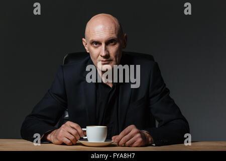 Gut aussehend Geschäftsmann am Tisch sitzen und Kaffee trinken, auf schwarzem Hintergrund - Stockfoto