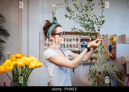 Schöne junge Frau Floristen arrangieren Pflanzen im Blumenladen lächelnd