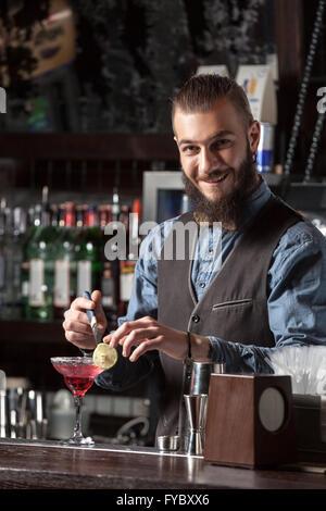 Glückliche junge Barkeeper cocktail an der Bar serviert. - Stockfoto