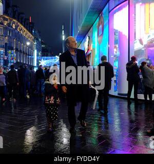 Mann Betrieb junges Mädchen an der Hand beim gehen auf nasser Fahrbahn in der Nacht in London - Stockfoto