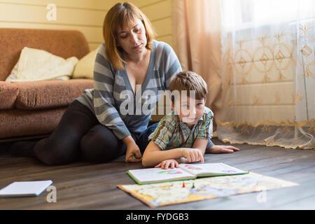Junge Frau mit ihrem kleinen Sohn sitzen auf dem Boden im Haus ein Buch zu lesen. - Stockfoto