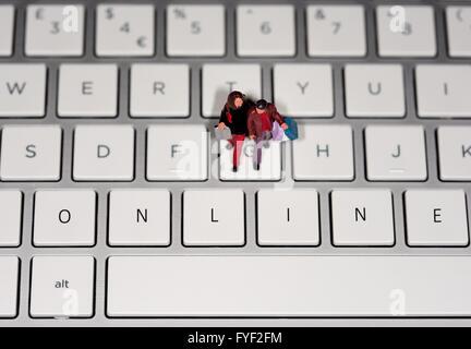 Ein Miniatur Figur paar Einkaufstaschen auf einer Laptoptastatur mit dem Wort ONLINE digital bearbeitete auf die - Stockfoto