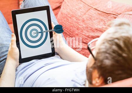 Genauigkeit, Geschäfts- oder mobile-marketing-Konzept: Hipster auf dem Sofa mit Dartscheibe Tablet. Die Bildschirmgrafik - Stockfoto