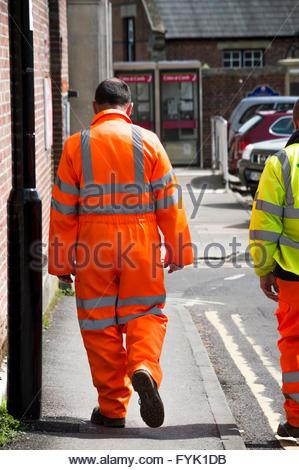 Mit Blick auf zwei Männer, die zu Fuß die Straße hinunter in hochsichtbare Arbeitsbekleidung, Blandford Forum, Dorset - Stockfoto