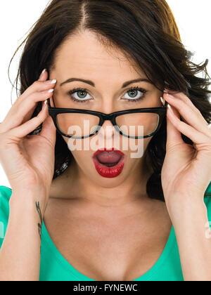 Schockiert, junge Frau, die über ihre Brille mit ihrem geöffneten Mund staunend vor einem weißen Hintergrund isoliert - Stockfoto