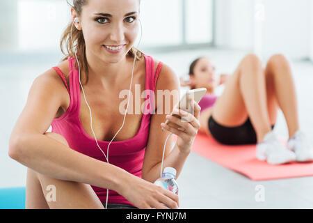 Junge lächelnde Frau in der Turnhalle eine Pause und anhören von Musik über ein smart Phone und Kopfhörer, Fitness - Stockfoto