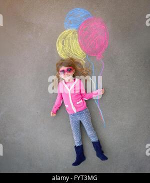 Ein kleines Mädchen mit Sonnenbrille hält kreative Kreide Ballons gezeichnet auf dem Bürgersteig für eine Phantasie, - Stockfoto