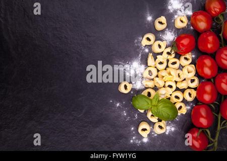 Tortellini, Tomaten, Basilikum und Mehl auf einem schwarzen Steinplatte. Draufsicht mit Exemplar - Stockfoto