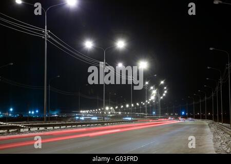 Nachtstraße mit Spuren von Licht der Scheinwerfer - Stockfoto