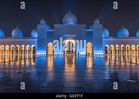 Sheikh Zayed Grand Moschee bei Nacht bedeckt mit schönen blauen Lichtern und Lichtstrahlen - Stockfoto
