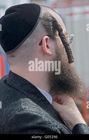 Nahaufnahme von einem extrem religiösen jüdischen Mann Peyot im Freien in Coney Island während des Passahfestes. - Stockfoto