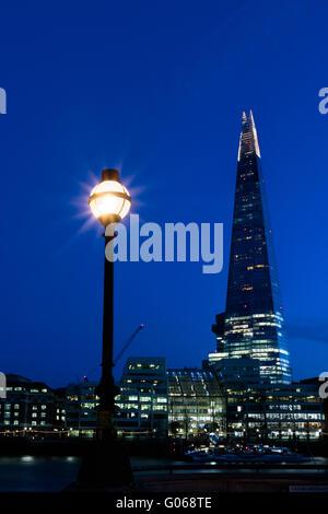 Nacht-Blick auf die Skyline von London zeigt The Shard und eine Straßenlaterne - Stockfoto