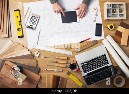 Bauingenieur und Architekt der Schreibtisch mit Hausprojekte, Laptop, Werkzeuge und Holz Farbfelder Draufsicht, - Stockfoto
