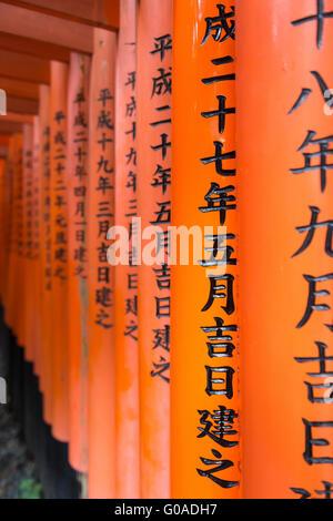 Nahaufnahme des Schreibens auf die roten Torii Toren am Fushimi Inari Schrein in Kyoto, Japan - Stockfoto