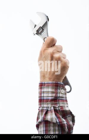 Männliche Hand, die einen verstellbaren Schraubenschlüssel auf weißem Hintergrund - Stockfoto
