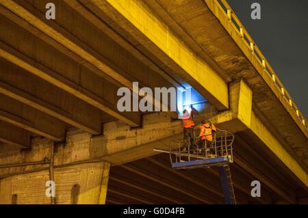 Arbeiter überprüfen eine Brücke Autobahn bei Nacht