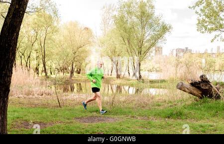 Ein senior Mann, getragen in schwarz und grün läuft in der Nähe des Sees bei einem frischen Frühlingstag - Stockfoto