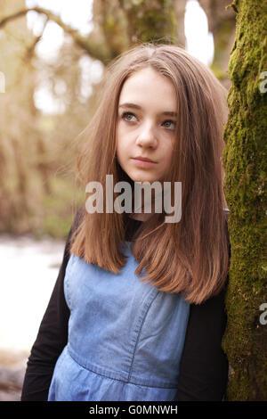 Ziemlich junges Mädchen auf der Suche nach oben während auf einem moosigen Baum gelehnt - Stockfoto