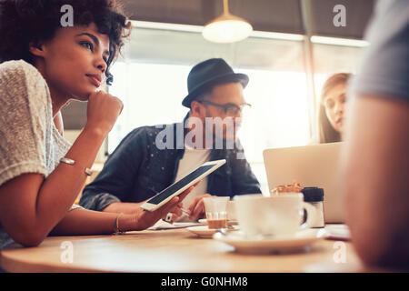 Porträt von Afrikanerin mit digital-Tablette und Menschen im Hintergrund an einem Cafétisch hautnah. Junge Freunde - Stockfoto