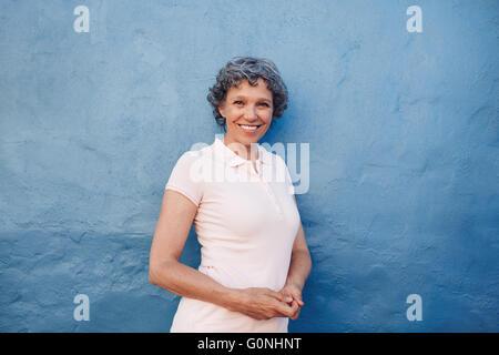 Porträt von lächelnden Reife Frau stand vor blauem Hintergrund. Attraktive senior weiblichen lehnt an einer Wand - Stockfoto